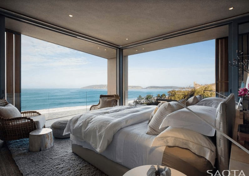 This master bedroom features an upholstered bed with a seating area on its end showcasing wicker chairs and round ottomans. It has recessed ceiling lights and panoramic windows overlooking a breathtaking beachfront view.