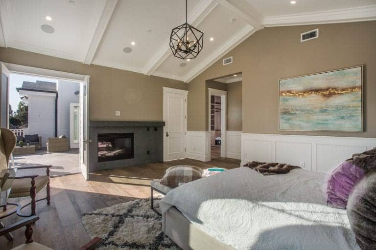 Cozy primary bedroom with wide plank flooring and a cathedral ceiling mounted with recessed lights and a geometric pendant. It includes a fireplace and an abstract painting mounted above the white wainscoting.
