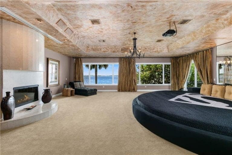 Spacious primary bedroom boasts a large round bed facing the fireplace with antique vases along with a tufted chaise lounge by the glass paneled windows overlooking the outdoor scenery. It has carpet flooring and a distressed tray ceiling mounted with a wrought iron chandelier.