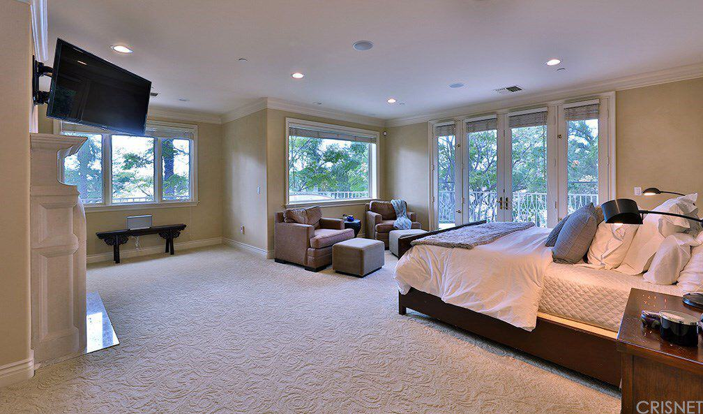 Beige master bedroom with textured carpet flooring and a French door leading out to the balcony. It includes a wall mount TV and a dark wood bed facing the brown armchairs paired with matching ottomans.