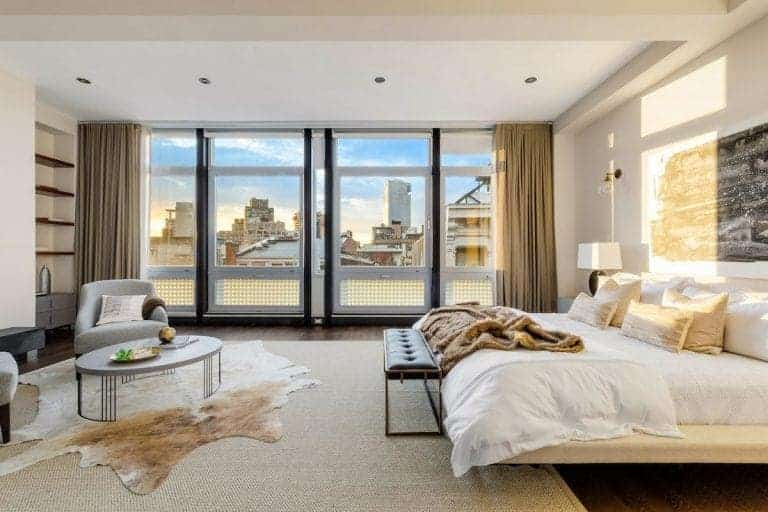 An abstract artwork hangs above the platform bed with a tufted bench on its end. It faces the gray armchairs and a round coffee table that sits on a cowhide and jute rugs.
