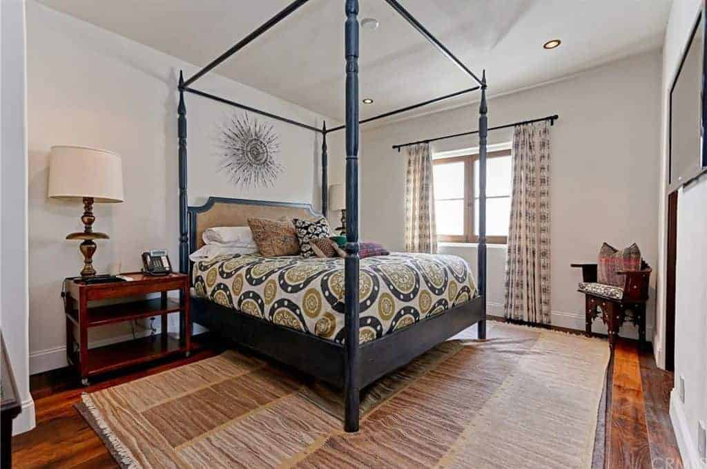A gorgeous sunburst mirror hangs above the canopy bed dressed in round patterned bedding. It is accompanied by a stylish seat and wooden nightstands that blend in with the rich hardwood flooring topped by a brown area rug.