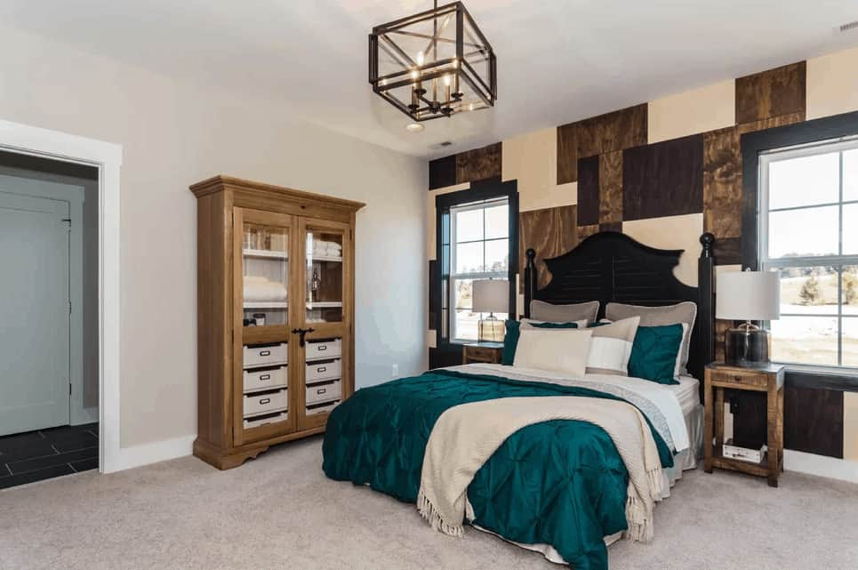 A glass cube chandelier hangs over the skirted bed flanked by black framed windows and wooden nightstands that are topped with drum table lamps. It is accompanied by a light wood display cabinet that's placed against the gray wall.