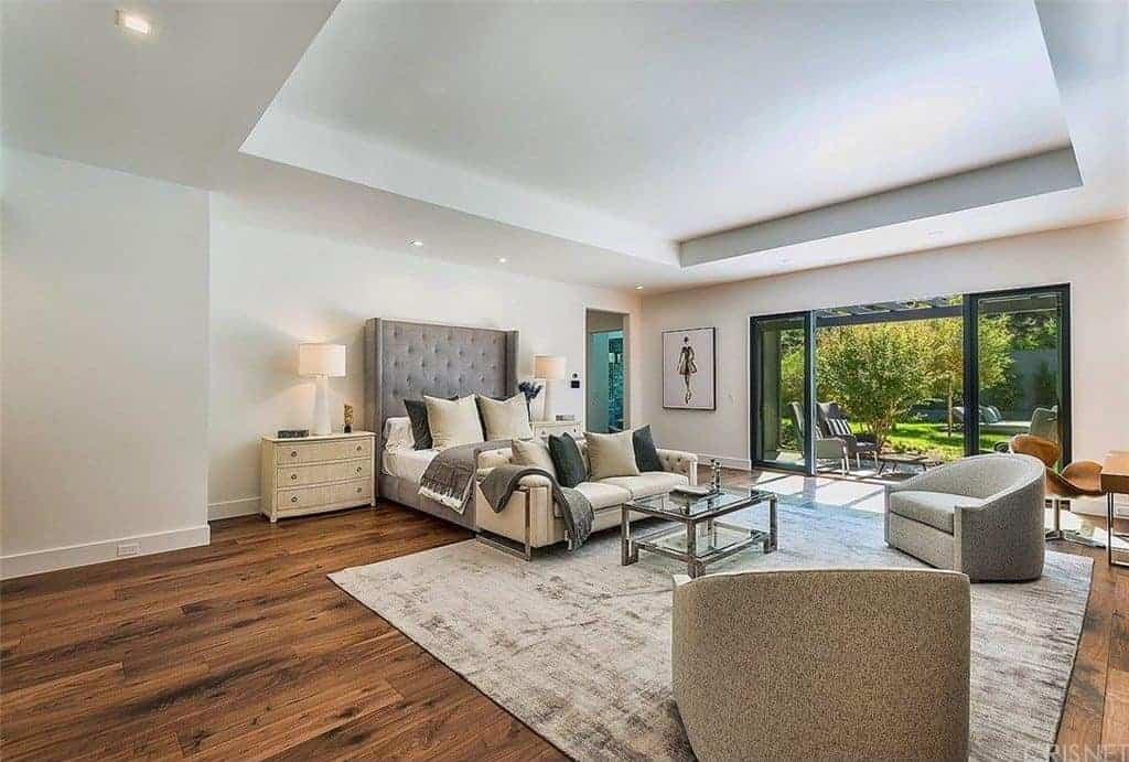 Spacious primary bedroom with hardwood flooring and glass sliders that open to the backyard. It includes a gray wingback bed and a seating area on its end featuring cozy seats surrounding a glass top coffee table over a distressed area rug.