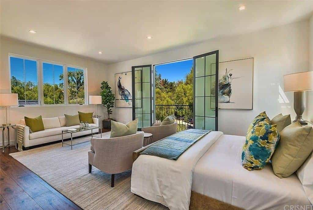 This primary bedroom is decorated with a potted plant and gorgeous artworks mounted on the white wall. It has a comfy bed and a seating area lighted by drum table lamps and recessed ceiling lights.