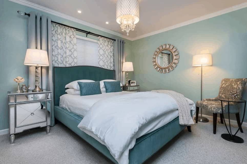 The fabulous master bedroom features a sunburst mirror and a printed chair facing the green upholstered bed that's illuminated by a lovely drum chandelier. It is flanked by mirrored nightstands and glass table lamps.