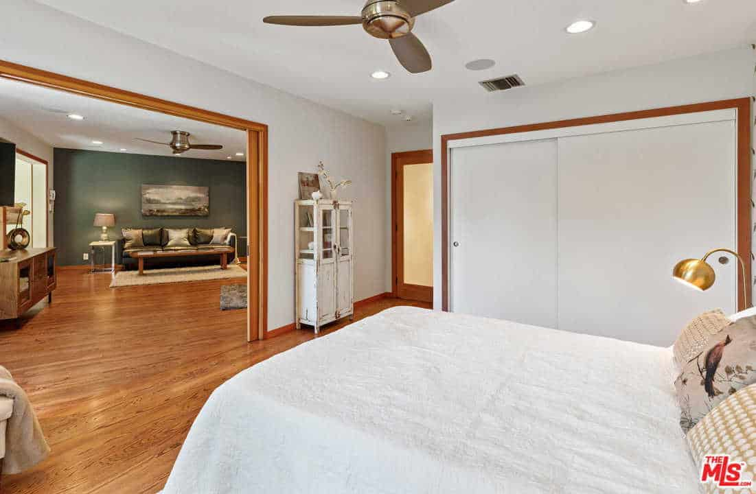 A chrome ceiling fan hangs over the comfy bed that's accompanied by a built-in wardrobe and a distressed cabinet against the white wall. There's a wooden sliding door in the middle that opens to the adjoining room.