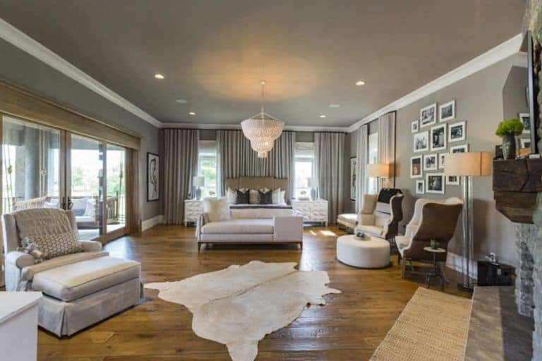 Gray master bedroom decorated with a photo gallery and a boho chandelier that hung over the cushioned bench. It has a cozy bed and seats along with cowhide and jute rugs that lay on the wide plank flooring.