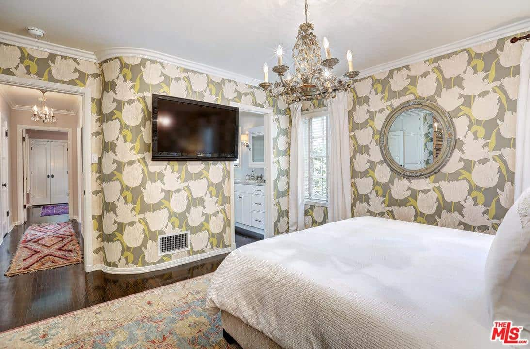 Clad in floral wallpaper, this master bedroom is decorated with a round mirror and a gorgeous candle chandelier that hung over the upholstered bed facing the wall mount TV.