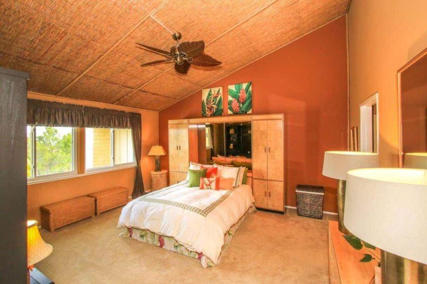 Primary bedroom with orange walls and a shed ceiling, along with carpeted flooring. The room offers a double-sized bed with two closet on both sides.