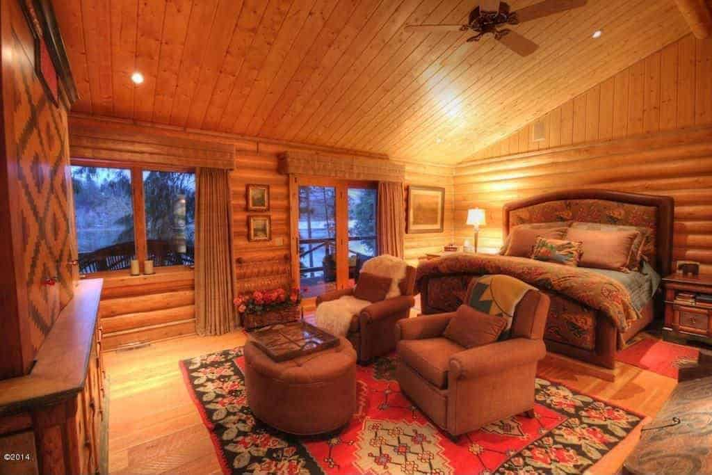 Rustic primary bedroom with logs walls and a tall shed ceiling. The room offers a large and elegant brown bed along with a pair of brown chairs with a brown ottoman.