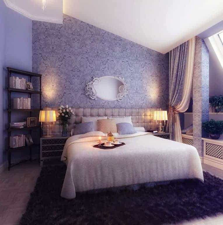 A primary bedroom with a gorgeous purple wall design and an elegant bed setup lighted by fancy table lamps on both sides.
