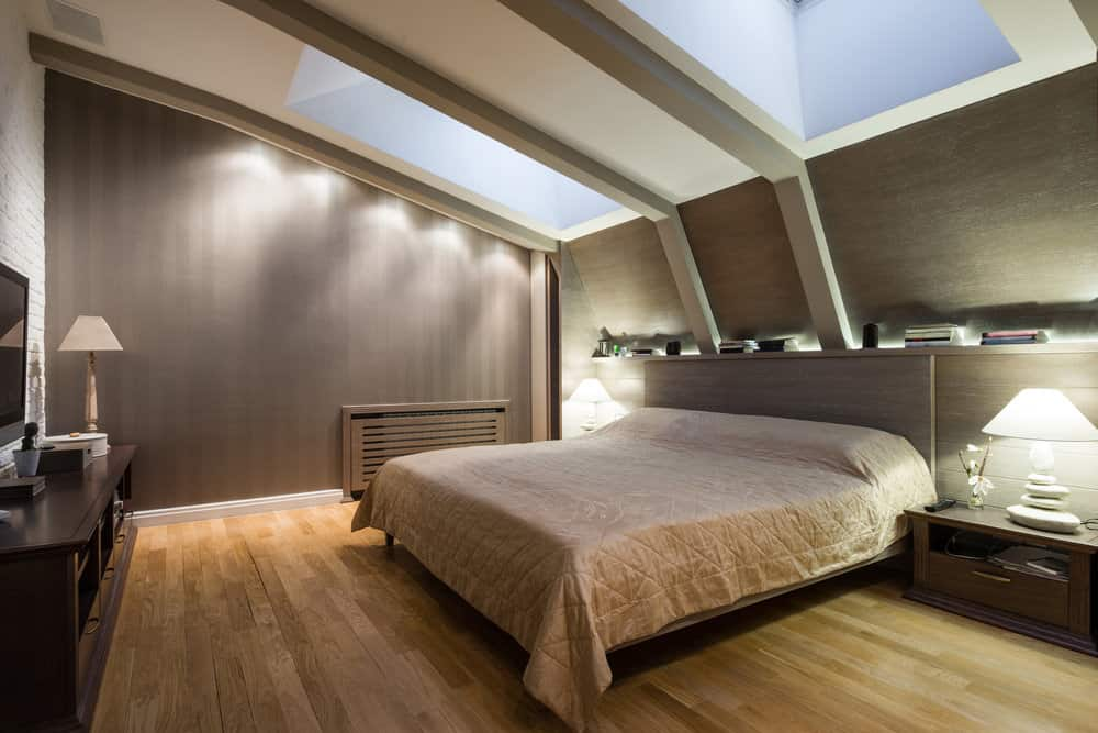 Modern primary bedroom with a shed ceiling featuring skylights. The room has brown walls and hardwood floors. It also offers a comfy bed lighted by two table lamps.
