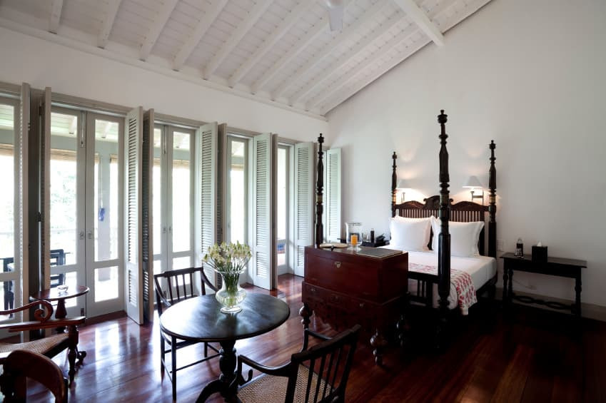 Primary bedroom with wood beam shed ceiling, a four-poster bed, seating areas, folding doors, and hardwood flooring.
