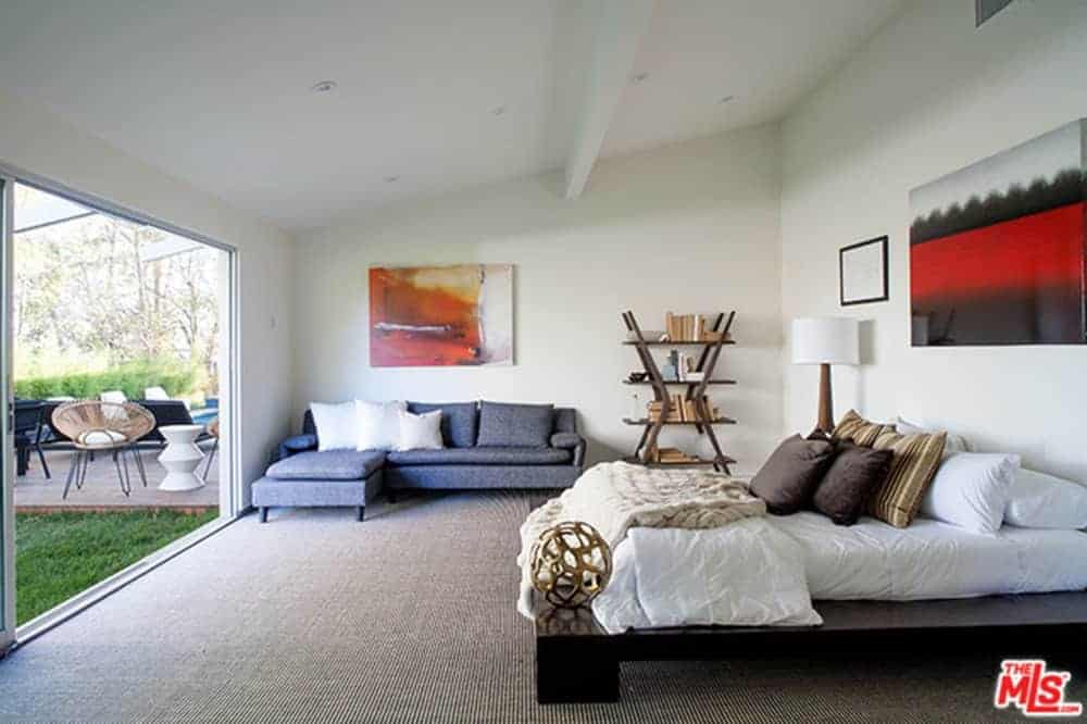 Primary bedroom featuring a cozy bed setup along with a modish couch on the side, surrounded by white walls and a white shed ceiling, along with carpeted flooring.