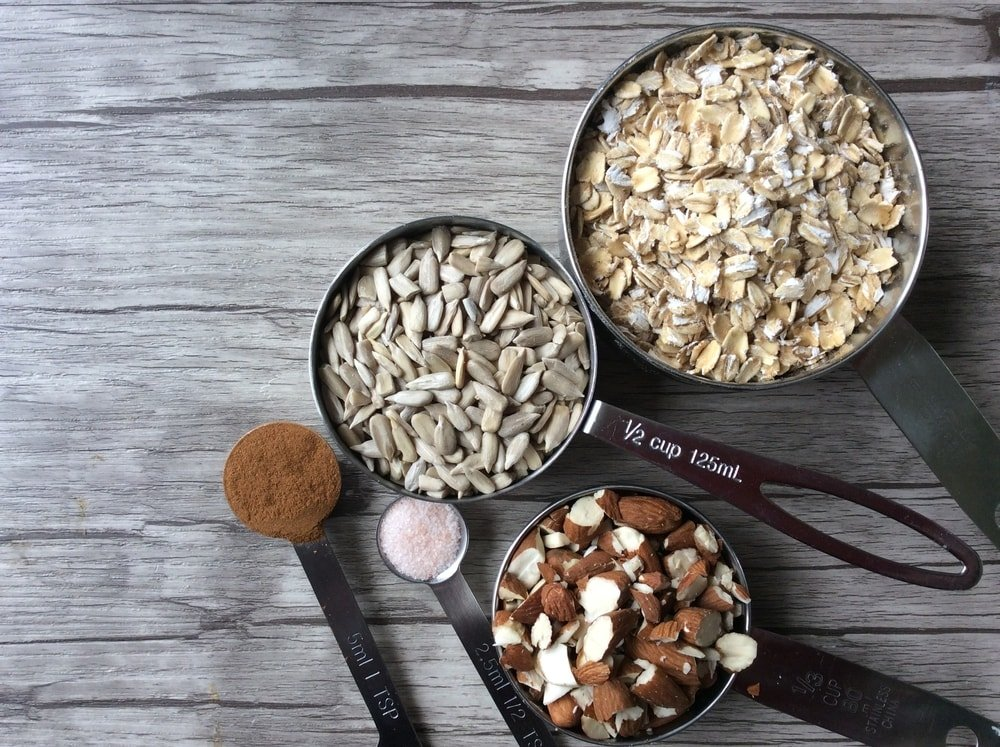 Measuring cups of various sizes filled with various nuts.