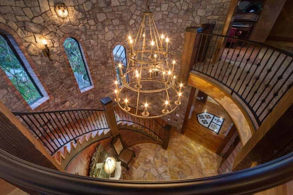 The Mediterranean-style foyer offers a seating area and a winding staircase fixed against the stone walls. It is illuminated by warm sconces along with a three-tier chandelier that hung from the tall ceiling. Photo Credit: Steve Haning Source:luxecir.idxbroker.com