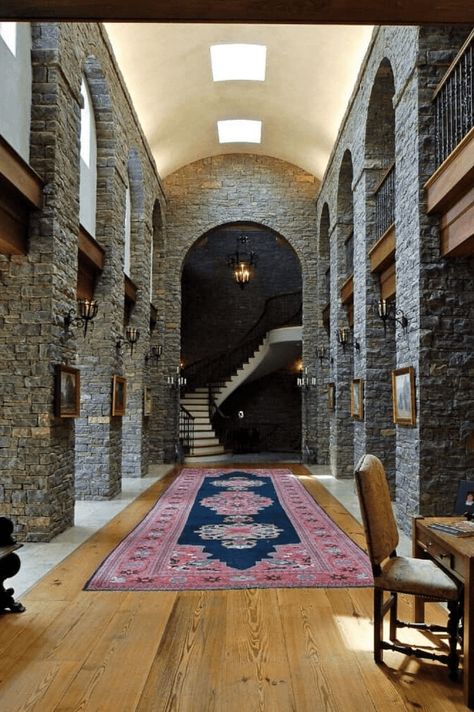 The classic foyer features a high barrel-vaulted ceiling fitted with skylights and wide plank flooring topped by a vintage area rug. The hallway is decorated with candle sconces and framed photos that are fixed against the stone brick walls.