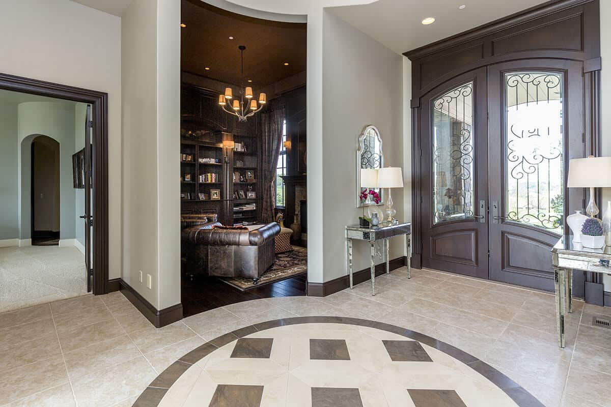The beige tiles of the flooring in this Mediterranean-style foyer is adorned with a pattern in the middle that has a dark brown hue matching the arched main double doors. This has glass panels and is flanked by two mirrored console tables bearing table lamps and decors.