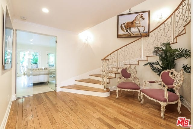 This warm and welcoming Mediterranean-style home has a classic feel to its hardwood flooring and the pair of wooden French armchairs with brown cushions. There is also a potted plant in the middle of these chairs that stands out against the beige walls.