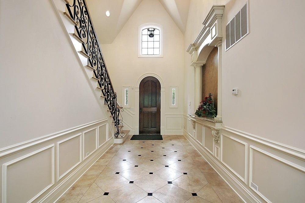 This Mediterranean-style foyer has beige flooring tiles patterned with small pitch dark tiles in between. This complements the white wooden walls that has a built-in arched alcove on the side that has a shelf and two small pillars.