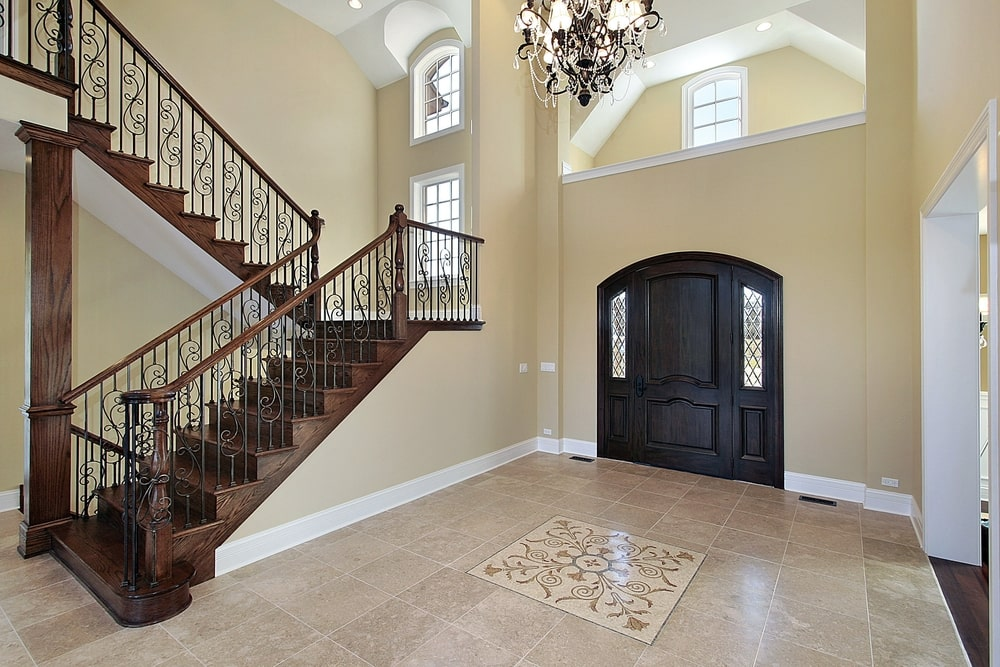 The beauty of this Mediterranean-style foyer stems from its simplicity. The beige walls are contrasted by the black wooden arched main door that has matching side lights. This also contrasts the beige flooring tiles with an intricate design in the middle underneath the chandelier.