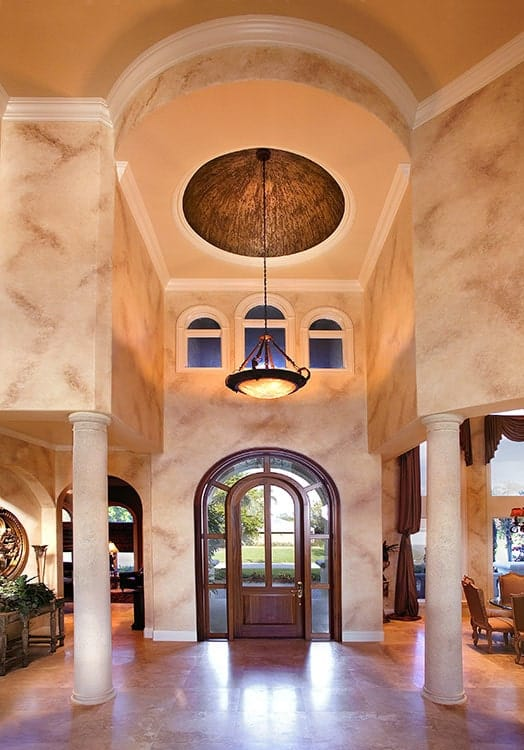 The beautiful arched main door has a dark wooden frame that supports glass panels that match with the side lighting and transom window. This brings in natural lights that brighten the beige walls and the two beige columns that stand out against the earthy floor tone.