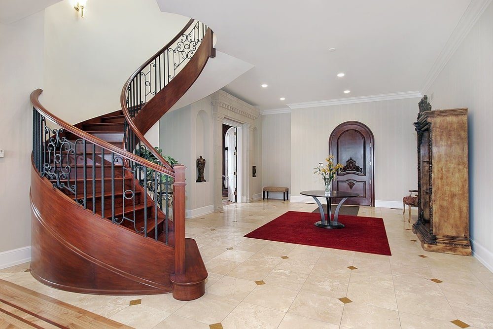 The arched wooden door has a dark brown tone that matches with the circular table on the red area rug as well as the wooden spiral staircase. This stands out against the light beige flooring tiles and the light gray walls and ceiling that has recessed lights.