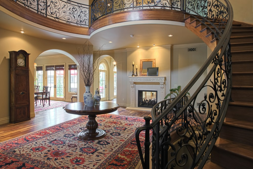 This is an elegant Mediterranean-style foyer that has a colorful patterned area rug covering most of the hardwood flooring that is matched with arched entryways and a fireplace on the far wall underneath the second floor landing that has wrought iron intricate railings.