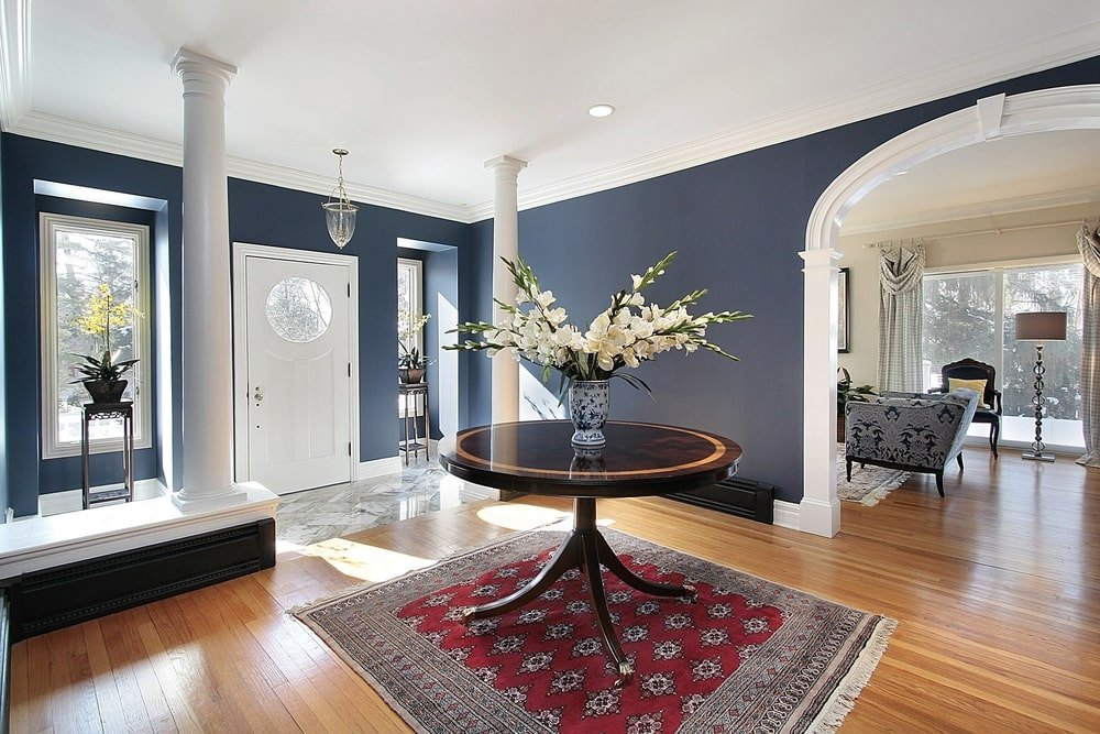 The navy blue walls of this Mediterranean-style foyer make the white pillars stand out as they flank the entryway from the white main door. This door has a tall glass window on either side that is adorned with potted plants on metal pedestals.