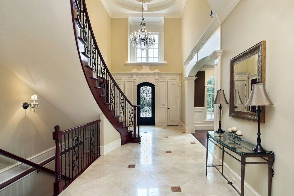 The wrought iron railings of the stairs matches with the railings of the main door that has a glass panel in the middle. This door is surrounded by a white wooden structure that has two smaller side doors and topped with a large transom window that brightens up the beige upper walls and the crystal chandelier.