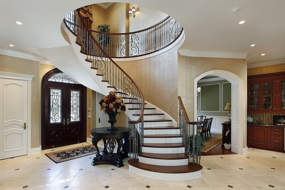 Beside the spiral staircase of this foyer is a black wooden round table that has a elegant designs and a matching black vase on top bearing colorful flowers. This is a perfect match for the black floral area rug that serves as a welcome mat to the wooden doors.