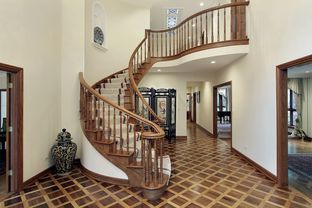 The spiral staircase of this foyer has wooden railings and wooden steps that is mostly covered with a beige carpet. This wooden staircase matches well with the hardwood flooring that has a checkered pattern that contrasts the simple white walls.