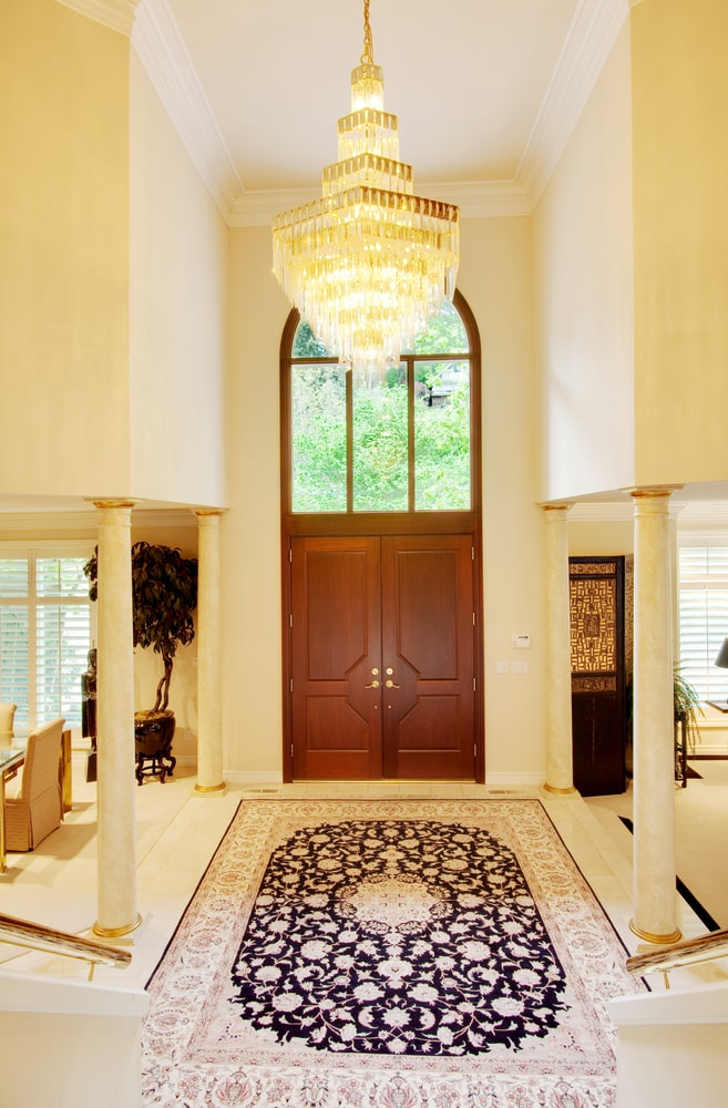 The stand-out element of this grand foyer is the massive crystal chandelier hanging over the large floral area rug flanked with thin beige pillars blending with the beige walls. These are contrasted by the wooden main door that has a large arched transom window.