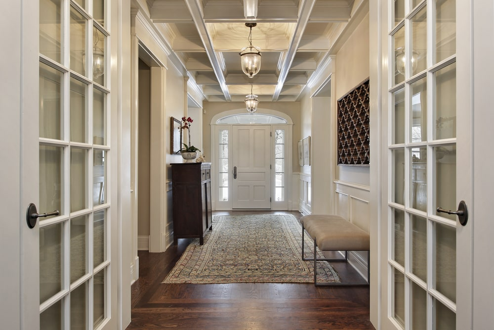 This hallway-type foyer has a beautiful coffered ceiling that hangs lantern pendant lights in intervals over the colorful patterned area rug that covers most of the dark hardwood flooring. This matches with the wooden cabinet on the opposite side of the cushioned bench.