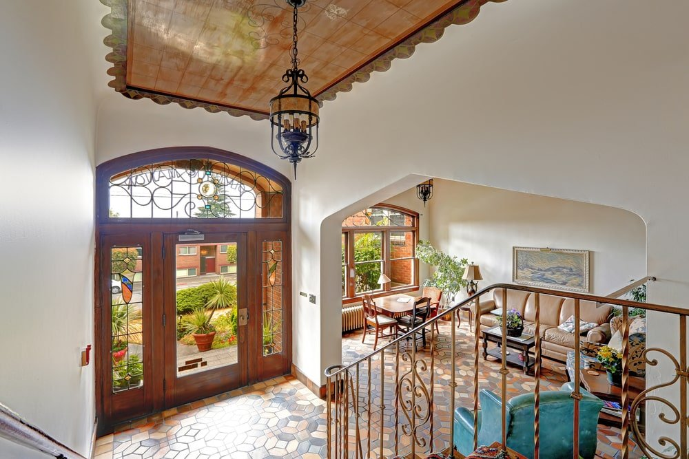 This charming Mediterranean-style foyer has a small flooring space adorned with mosaic patterned tiles that are brightened by the abundant natural lighting from the glass panels of the main door, its side lights and the transom window that has wrought iron matching the large pendant light and the railings of the stairs.