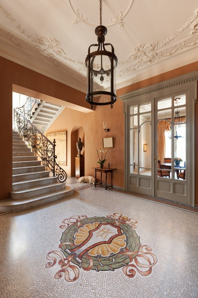 This Mediterranean-style foyer has white mosaic flooring with a large crest design in the middle. This is paired with a white ceiling elegant intricate designs on it elevating the elegance of the foyer and the large lantern pendant light that stands out against the earthy orange wall