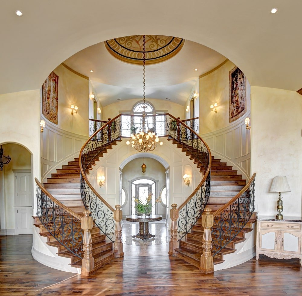 This elegant Mediterranean-style foyer has double stairways with the same wooden steps that match the hardwood flooring. The middle of this foyer has a dark wooden round table bearing plants that is brightened by the natural lights from the glass panels of the main door.