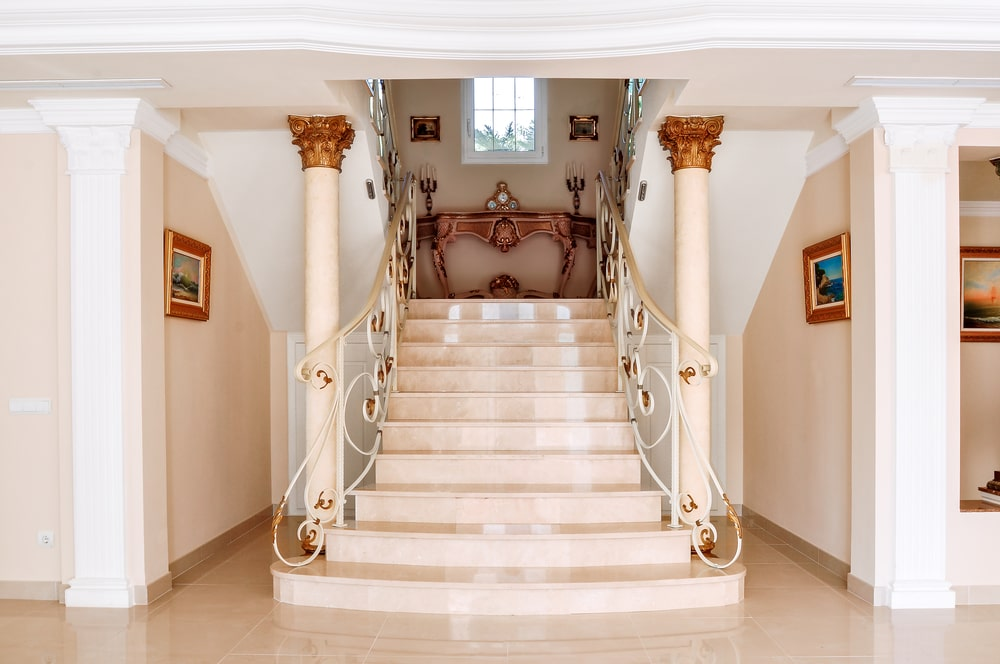 The beautiful pink flooring matches with the walls and the two pink pillars that are flanking the stairs with the same light pink hue. These are all adorned with small patches of gold on the intricate railings of the stairs as well as the tops of the pillars.