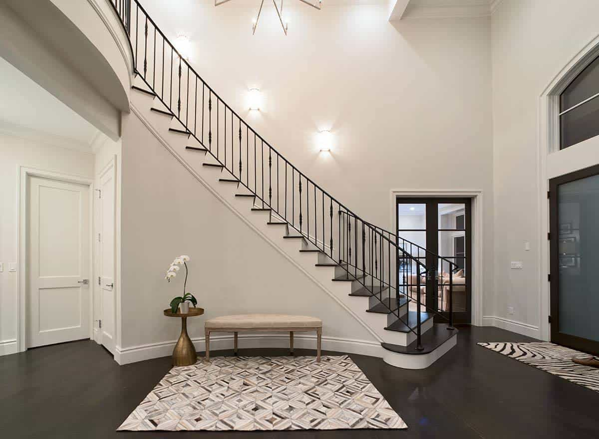 This is a simple Mediterranean-style foyer that has a cushioned bench at the side of the stairs. This bench is paired with a brass side table bearing a flower in a pot. This stands out against the light gray walls just as the patterned area rug stands out against the black hardwood flooring.