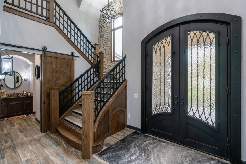 The black arched main doors are adorned with frosted glass panels supported by intricate wrought iron railings matching the railings of the wooden staircase beside the main doors. Beside this is a small bathroom that has a wooden sliding door.