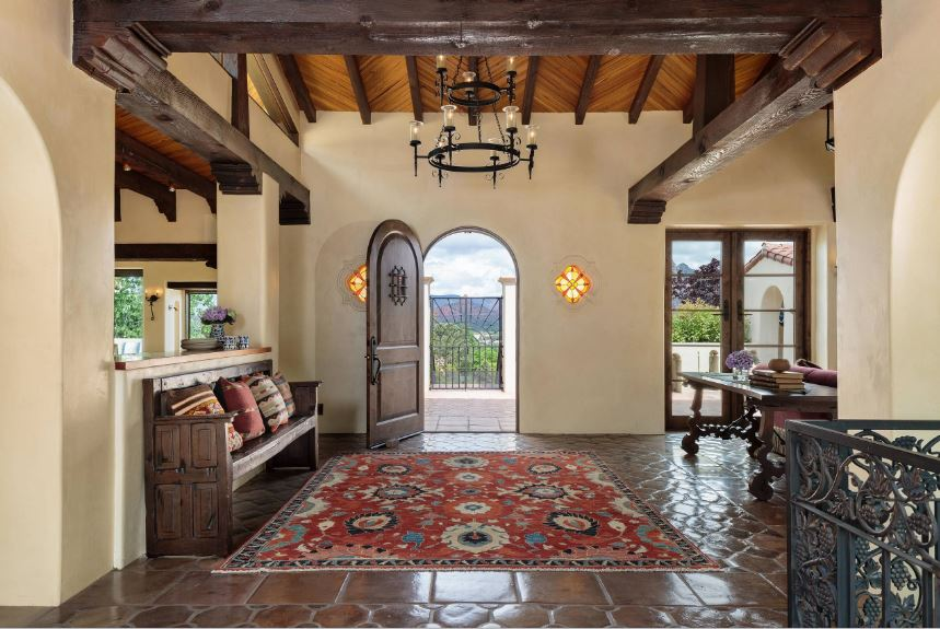 This beautiful foyer boasts of dark terracotta flooring tiles that blends with the dark wooden bench and the dark arched wooden main door. This also pairs well with the wooden exposed beams of the ceiling that contrast the beige walls.