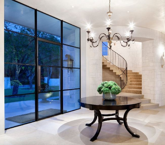 This foyer is dominated by the blue tinted wall of glass that also houses the glass main door with the same tinted glass. This gives a wonderful contrast to the light beige flooring, white walls and white ceiling that hangs a dark iron chandelier over the round dark wooden table.