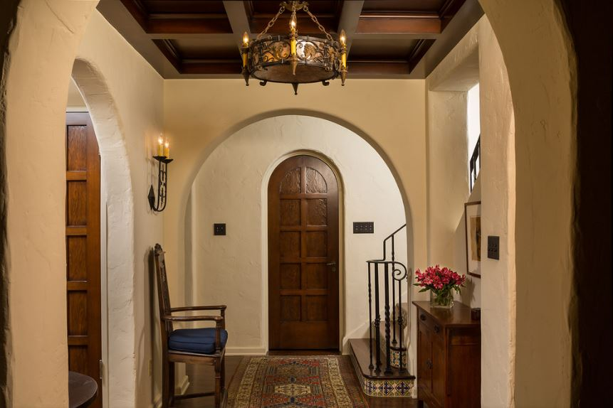This small and cozy foyer has arched entryways to match the arched wooden door and the wooden coffered ceiling that supports a dark brown chandelier. This pairs well with the dark hardwood flooring that is mostly covered by a colorful patterned area rug.