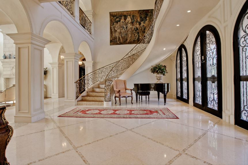 This spacious and bright grand foyer is dominated by the presence of the large classical painting mounted by the spiral staircase. This is a nice complement to the grand piano that stands out against the light beige flooring and walls but matches with the frames of the arched doors.