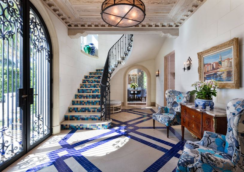 This impressive Mediterranean-style foyer has a warm welcome for the guests with its cushioned armchairs with blue patterns that pair well with the blue tiles on the patterned flooring. This is brightened by the wrought iron double doors.