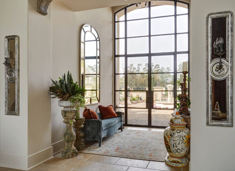 The brightness of this Mediterranean-style foyer is mostly due to the large glass wall that also houses the glass main door. This is reflected by the arched mirror mounted above the blue velvet cushioned bench adorned with jars and potted plants on wooden pedestals.