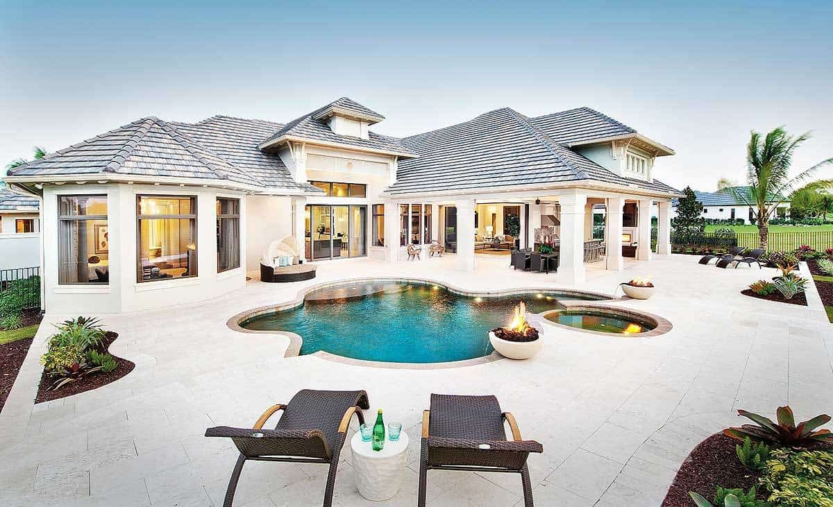 The bright exterior walls that seem to blend with the bleached concrete flooring of the backyard makes the irregular-shaped pool to stand out. This is surrounded by various sitting areas with lawn chairs and colorful miniature gardens as well as a couple of firepits for warmth.