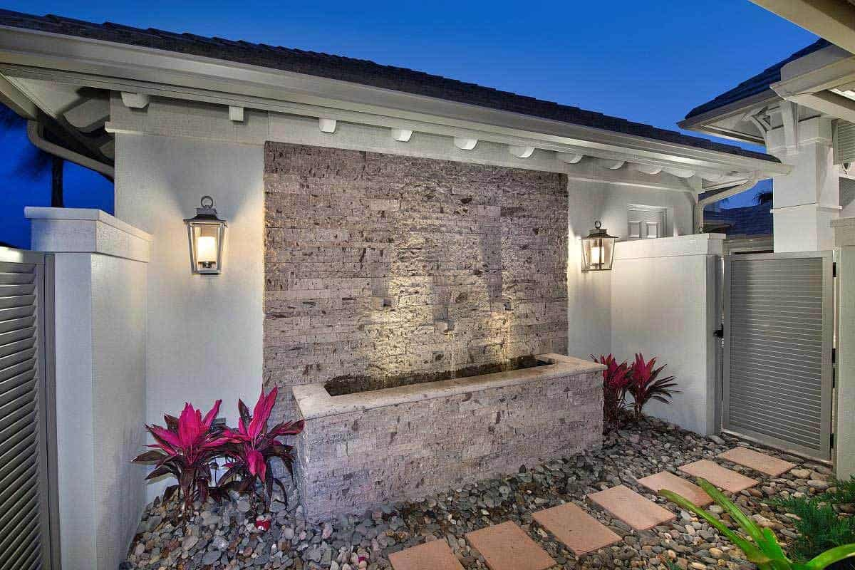 This is the small area at the side of the home in between the outer side gate and the gate to the backyard. It has a walkway of terracotta blocks embedded into gravel-filled soil that is adorned with colorful shrubs and a stone fountain against the wall.