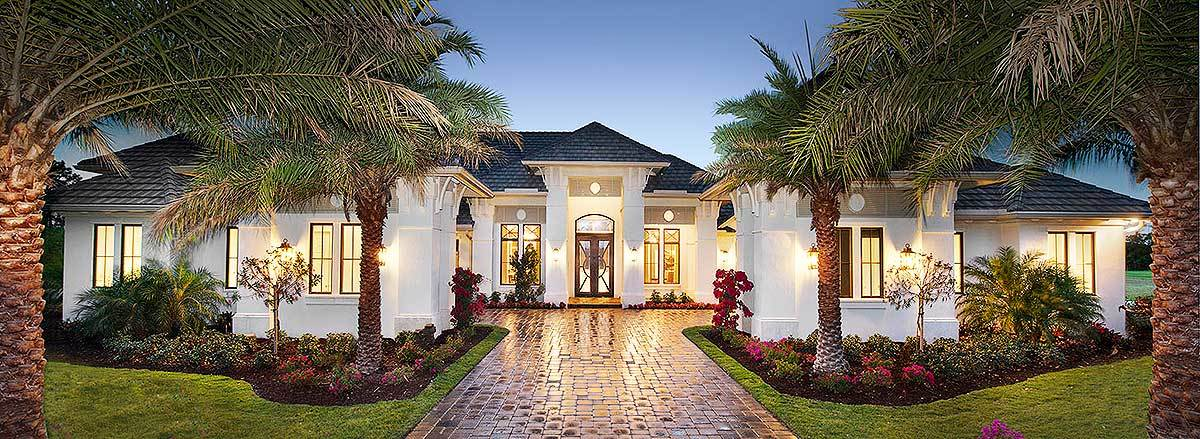 The terracotta walkway leading to the white exterior walls of the Mediterranean-style home is flanked with beautiful palm trees and colorful shrubs that stand out against the bright white exteriors and glowing windows. This presents a welcoming embrace for the guests that walk up to the glass main door under the arched entryway.